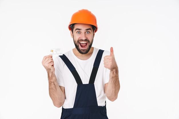 親指を上に表示しているクレジットカードを保持している白い壁の上に分離されたヘルメットのショックを受けた幸せな若い男のビルダーの肖像画。