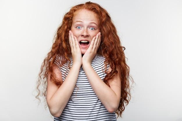 놀란 표정으로 카메라를보고 생강 머리와 주근깨가있는 충격을받은 어린 소녀의 초상화, 뺨을 만지고, 입을 크게 벌리고 눈, 흰색 배경 위에 절연 스탠드.