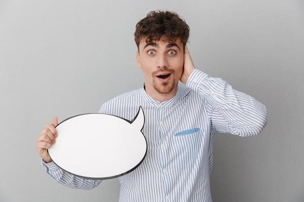 灰色の壁に分離された空白のコピースペース思考バブルを保持しているシャツに身を包んだショックを受けた男の肖像画