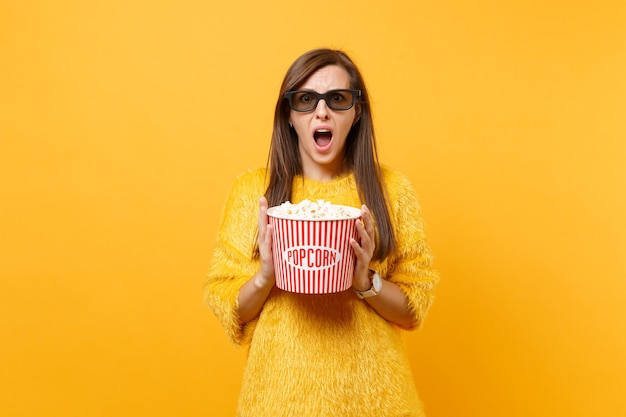 모피 스웨터를 입은 겁에 질린 어린 소녀의 초상화, 영화 영화를 보는 3d 아이맥스 안경, 밝은 노란색 배경에 격리된 팝콘 양동이를 들고. 영화, 라이프 스타일에서 사람들은 진실한 감정.