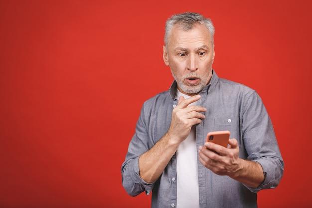 Портрет сотрясенного старшего человека в вскользь задыхаясь раскрывая рте от беспокойства и сюрприза держа мобильный телефон, смотря в камере изолированной над красной стеной.
