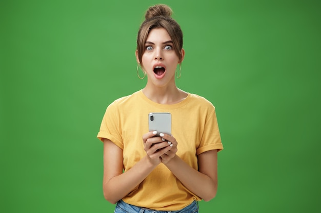 緑の壁の上のクールなアプリに反応して興奮から顎を落とし、スマートフォンを保持している黄色のtシャツで櫛の髪を持つショックを受けた無言で感動した美しい白人少女の肖像画。