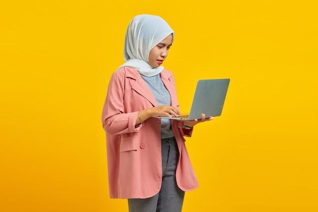파란색 배경에 격리된 랩톱 컴퓨터를 들고 서 있는 놀란 소녀의 초상화