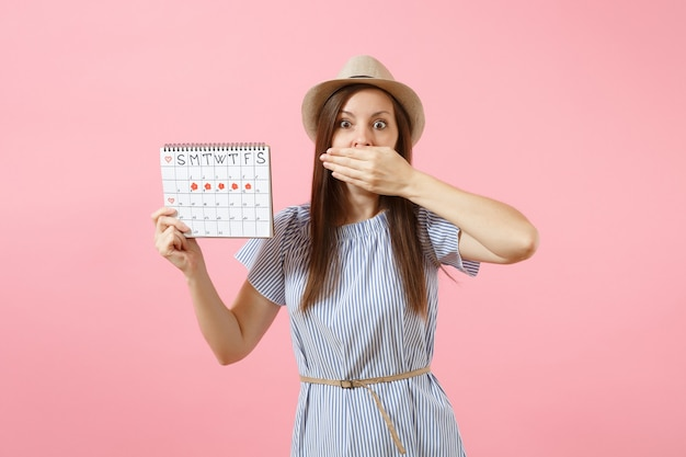 파란 드레스를 입은 충격받은 여성의 초상화, 밝은 추세의 분홍색 배경에 격리된 생리일을 확인하기 위한 기간 달력을 들고 있는 모자. 의료, 건강 관리, 부인과 개념입니다. 복사 공간