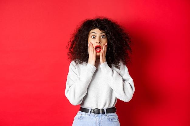ショックを受けた女性の肖像画は驚いて悲鳴を上げ、顔に触れ、印象的なプロモーションオファーでカメラを見て、赤い背景のスウェットシャツに立っています