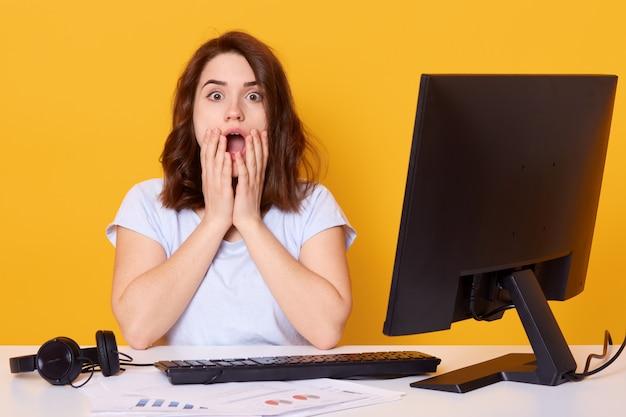 Портрет потрясенной женщины, сидящей за белым столом возле компьютера, с раскрытым ртом и широко открытыми глазами