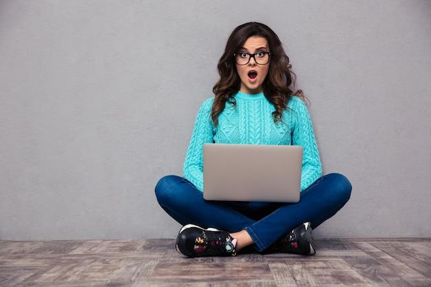 ノートパソコンと灰色の壁の床に座ってショックを受けた女性の肖像画