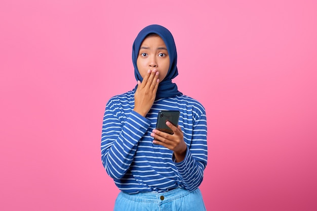 スマートフォンを保持し、手で口を覆うショックを受けた若いアジアの女性の肖像画