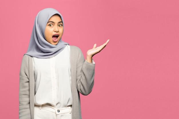 手のひらで製品を示すショックを受けた若いアジアの女性の肖像画