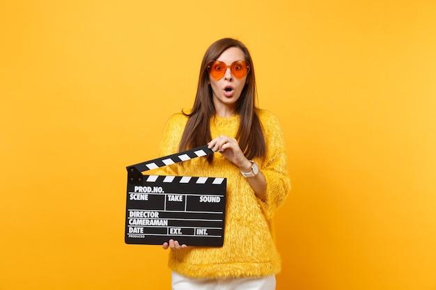 毛皮のセーター、黄色の背景で隔離のカチンコを作る古典的な黒のフィルムを保持しているオレンジ色のハートのメガネでショックを受けた若い女性の肖像画。人々は誠実な感情、ライフスタイル。広告エリア。