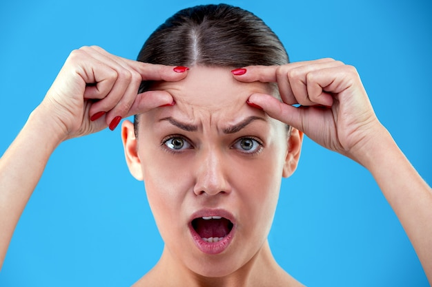 Портрет потрясен молодой женщины с разочарованием смотрит на камеру, касаясь ее морщины на лбу на синем фоне