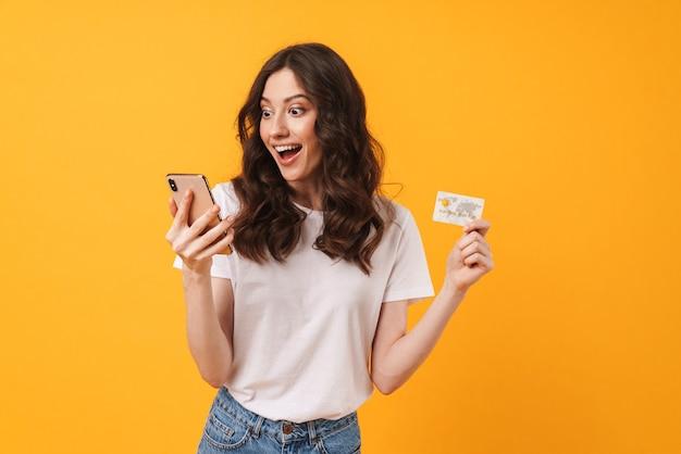 Портрет потрясенной молодой женщины, позирующей изолированной над желтой стеной, используя мобильный телефон, держащий дебетовую карту.