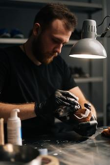 수리할 낡고 옅은 갈색 가죽 신발에 청소용 거품을 바르는 제화공의 초상화