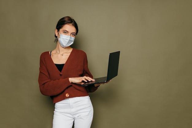 Портрет короткошерстной девушки в защитной маске с защитным снаряжением, использующей ноутбук, работающий удаленно во время mers cov ncov-2.