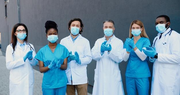 医療用マスク、手袋、白いガウンに立って、拍手喝采し、カメラを見ている若い男性と女性の医師の混血のショットの肖像画。多民族の医者。 covid-19勝利のコンセプト。拍手。