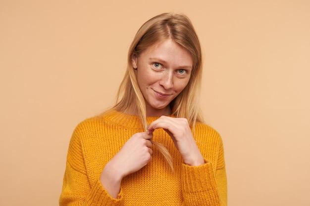 恥ずかしがり屋の緑色の目の若い赤毛の女性の肖像画は、上げられた手で髪を引っ張って恥ずかしそうに見て、ベージュに立っています