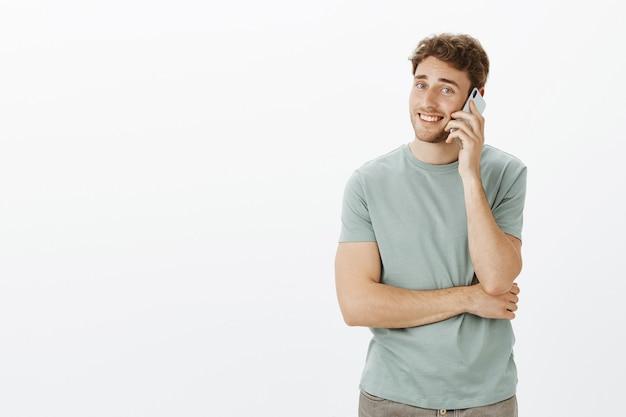 毛で恥ずかしがり屋のハンサムな男の肖像、スマートフォンで話していると広く笑顔