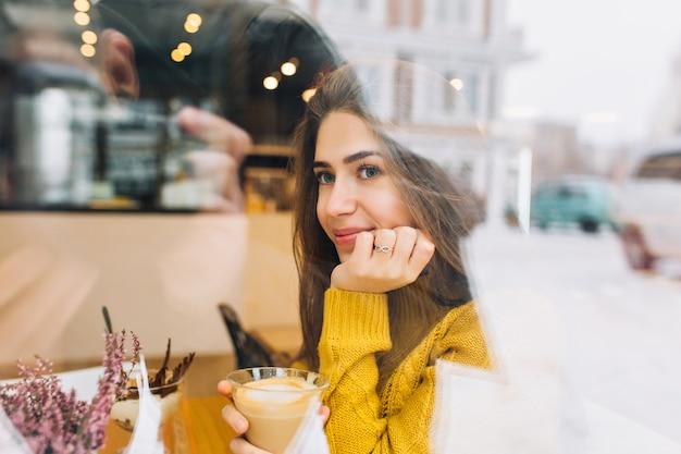 Портрет застенчивой задумчивой женщины в связанном свитере, наслаждаясь кофе и смотря улицу. фотография в помещении романтичной молодой женщины в желтом наряде, мечтающей о чем-то во время обеда в кафе.