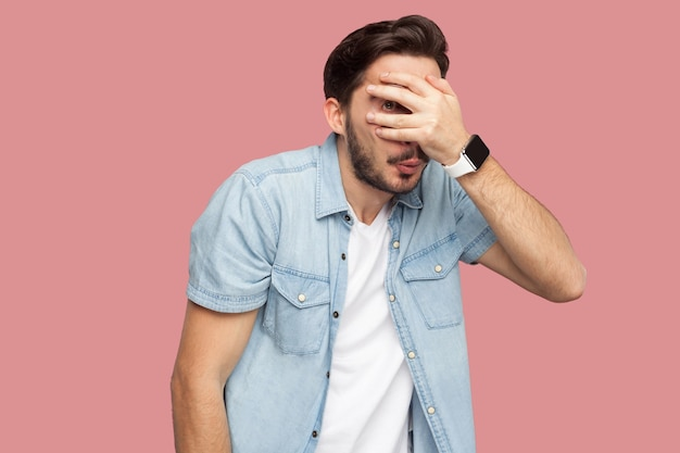 Портрет застенчивого, напуганного или выглядывающего бородатого молодого человека в синей рубашке повседневного стиля, стоящего, прикрыв глаза и смотрящего в камеру сквозь пальцы. крытая студия выстрел, изолированные на розовом фоне.