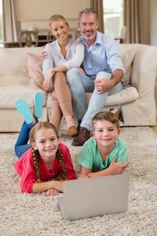 両親がソファに座っている間に敷物の上に横たわる兄弟の肖像画