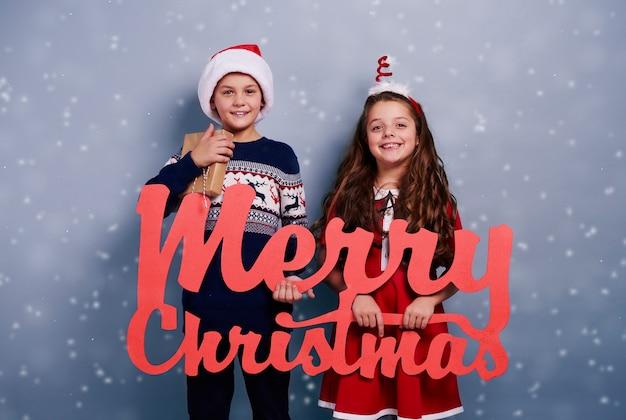 눈이 떨어지는 가운데 크리스마스 장식으로 형제 자매의 초상화