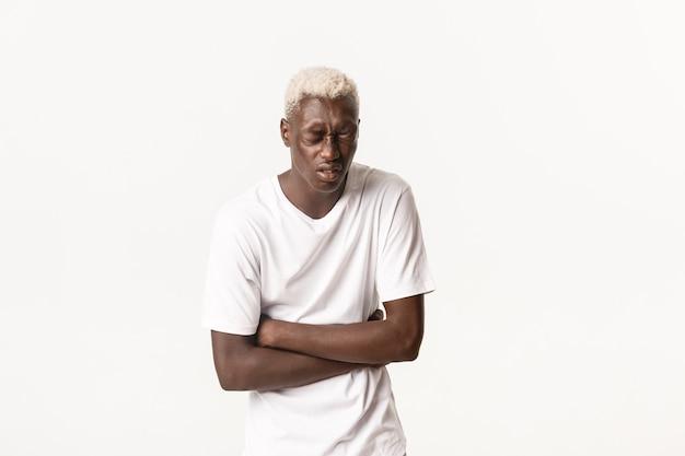Портрет больного афро-американского белокурого парня, сгибающегося от боли в животе, сильной боли, пищевого отравления