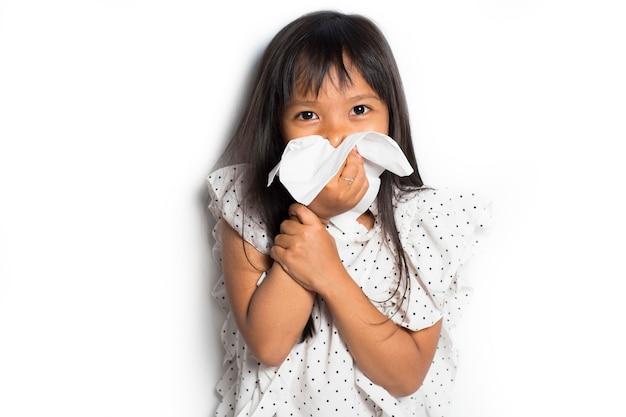 ティッシュで鼻を拭いて掃除する病気のアジアの小さな子供の女の子の肖像画