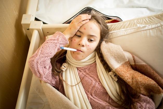 Портрет больной ветряной оспой девушки, лежащей в постели и измеряющей температуру