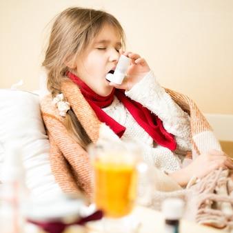 Портрет больной девушки с респираторным заболеванием, лежащей в постели и использующей ингалятор