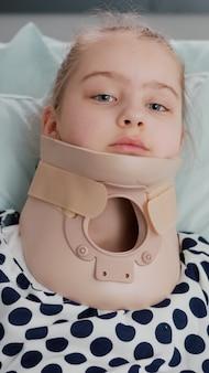 病棟での痛みを伴う手術後に首の頸部カラーが回復している間、カメラを見ながらベッドで休んでいる病気の小さな患者の肖像画。検査中に酸素経鼻チューブを着用している子供