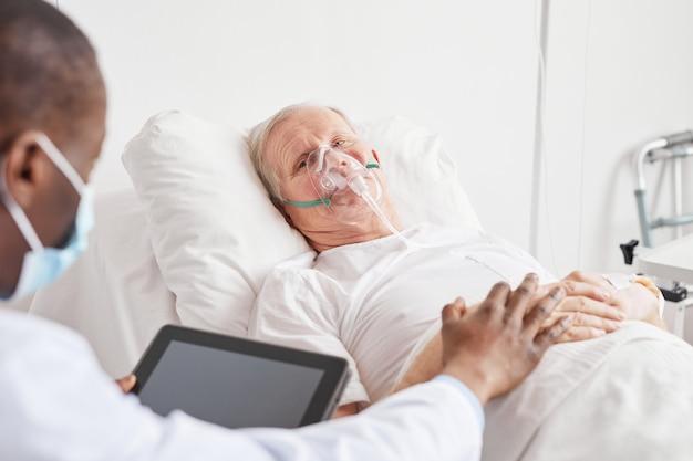 Портрет больного старшего мужчины, лежащего на больничной койке с кислородной маской и разговаривающего с афро-американским доктором, утешающим его, копия пространства