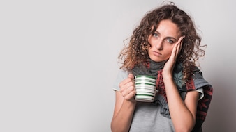 Portrait of sick woman holding coffee mug against gray background