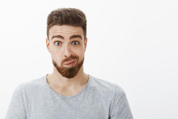 수염, 콧수염 및 파란 눈을 가진 어리 석고 재미있는 잘 생긴 남자의 초상화는 거울을보고 불확실한 어색한 얼굴을 만들고 회색 벽에 포즈를 취하는 변화에 대해 생각하고 있습니다.