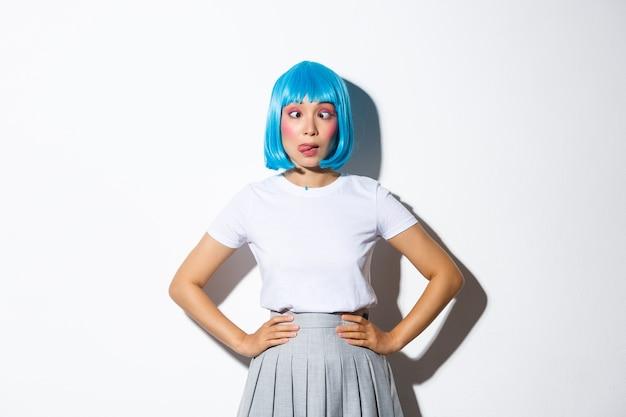 青いかつらとパーティー衣装で愚かなアジアの女の子の肖像画は、ハロウィーンの衣装で立って、舌を見せて、目を細めて変な顔をしています。