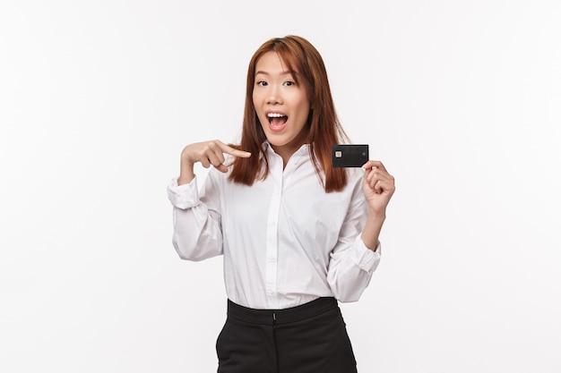 シャツとスカートで愚かなかわいいアジアの女性の肖像画、クレジットカードを指して、笑顔、銀行サービスを宣伝、オンラインで購入、インターネット決済、白い壁に立つ