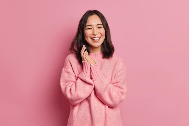 誠実なブルネットのアジアの女性モデルの肖像画は手のひらをこすり、笑顔は広く幸せを表現します喜びを感じます歯は特大のカジュアルセーターを着ています