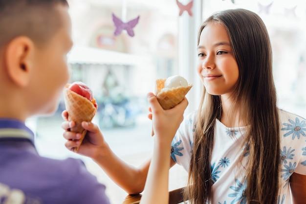 Портрет сестры с братом, которые едят мороженое во время обеда дома.