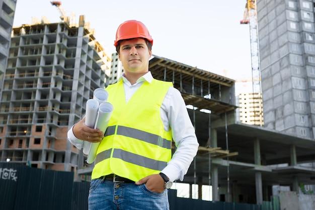 Портрет менеджера сайта, позирующего с чертежами на фоне недостроенного здания