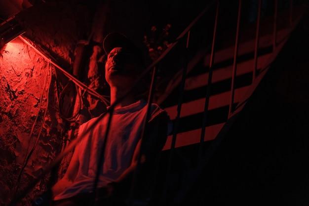 색된 붉은 빛과 어두운 배경으로 계단에 앉아 성인 남자의 초상화.