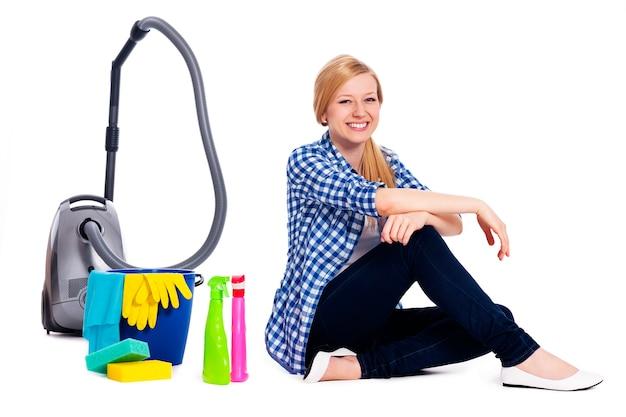 Портрет сидящей женщины с аксессуарами для уборки