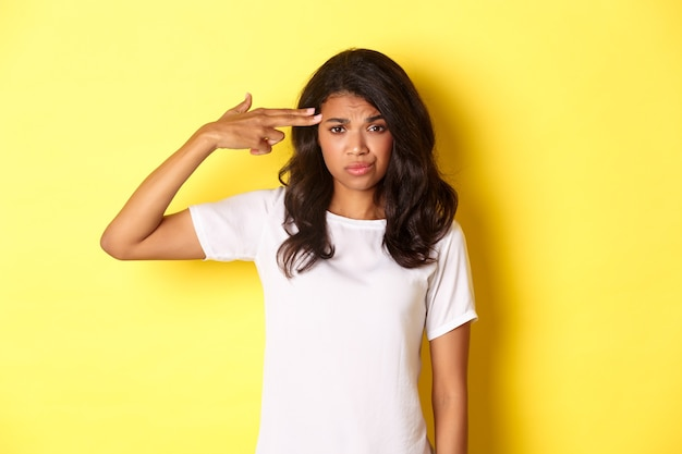 Портрет скептически настроенной и обеспокоенной афроамериканской женщины, делающей знак пистолетом над головой