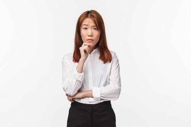 Портрет скептической и сомнительной молодой азиатской женщины в офисе, слушающей историю друга и выражающей недоверие, подозрительно глядя, как думают, что кто-то говорит ложь, стоит белая стена