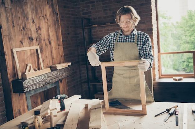彼のウッドショップでポーズをとる熟練したひげを生やした職人の肖像画