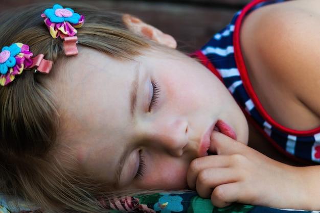 眠っている間に彼女の指を吸う眠っているかわいい子供の女の子の肖像画。子供のヘルスケアと幸福の概念。昼寝をしているベッドの中で平和な愛らしい子供の写真。良い夢を。おやすみなさい。