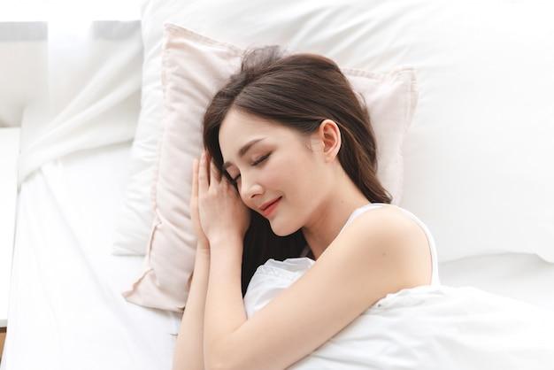 잠자는 젊은 아시아 여자의 초상화를 즐기고 집에서 침실에서 가까운 눈으로 침대에 누워 휴식을 취하십시오. 아시아 아름다움