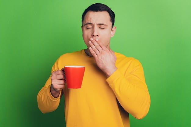 眠そうな夢のような男の肖像画緑の背景にコーヒーあくびパームカバー口を飲む