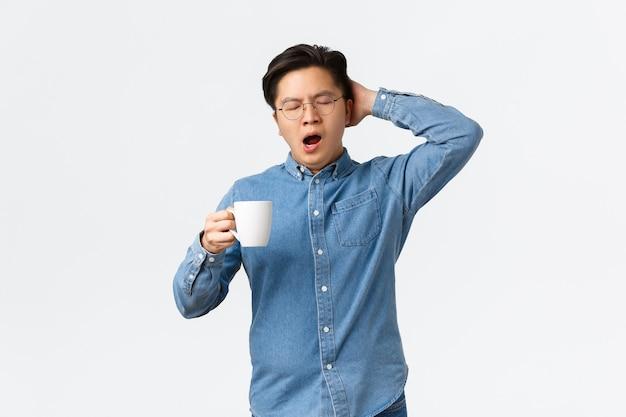 Портрет сонного молодого сотрудника мужского пола, зевая и держа кружку с кофе, просыпаясь усталым. человек работает поздно, желая спать, держа голову и закрыть глаза, стоя на белом фоне.