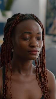 蓮華座に座って体の筋肉を伸ばして体を温めるスリムフィットの黒人女性トレーナーの肖像...