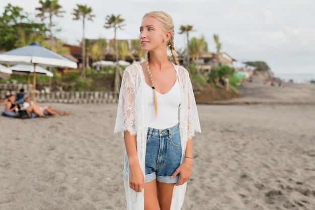 Портрет стройной загорелой блондинки с длинными волосами, красивой улыбкой, одетой в белую блузку и джинсовые шорты