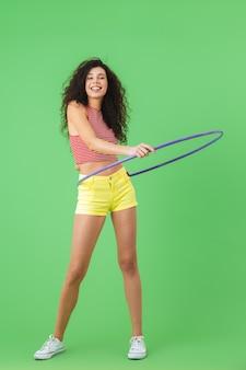 Портрет стройной женщины 20 лет в летней одежде, делающей упражнения с обручем во время гимнастики на зеленой стене